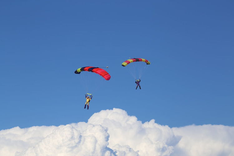 Scenic View Of People Paragliding Against Blue Sky