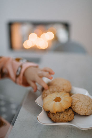 Midsection of woman holding cookies on table at home