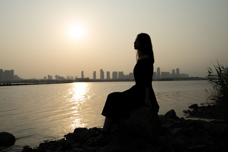 Woman looking at sea against sky during sunset
