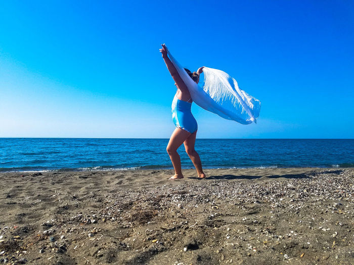 Full length of girl standing at beach against blue sky