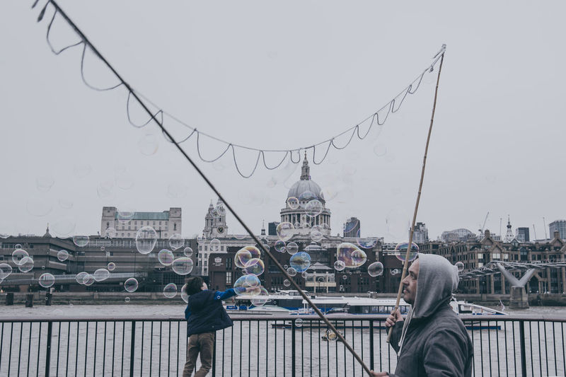 A boy plays with bubbles at Thames Shoreline in London on a cloudy and cold November day ... Architecture Bridge Bubble Bubbles Kids London Bridge LONDON❤ Picturing Individuality River Thames Seeing The Sights Shoreline Showcase: November Sphere Youth Of Today The Street Photographer - 2016 EyeEm Awards
