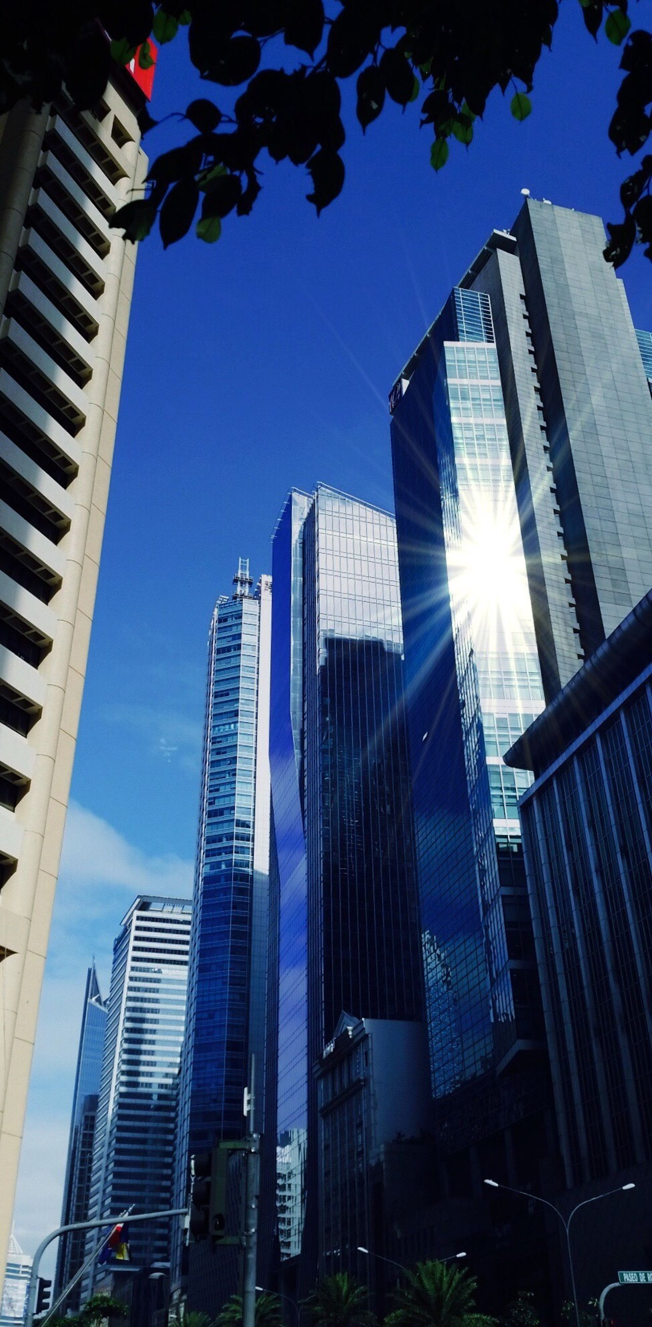 building exterior, architecture, skyscraper, city, built structure, tall - high, modern, office building, tower, low angle view, sun, sunlight, financial district, urban skyline, city life, sunbeam, building, clear sky, tall, sky