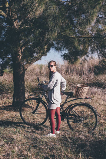 Portrait of young woman with bicycle standing on field