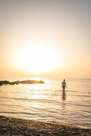 Silhouette person in sea against sky during sunset