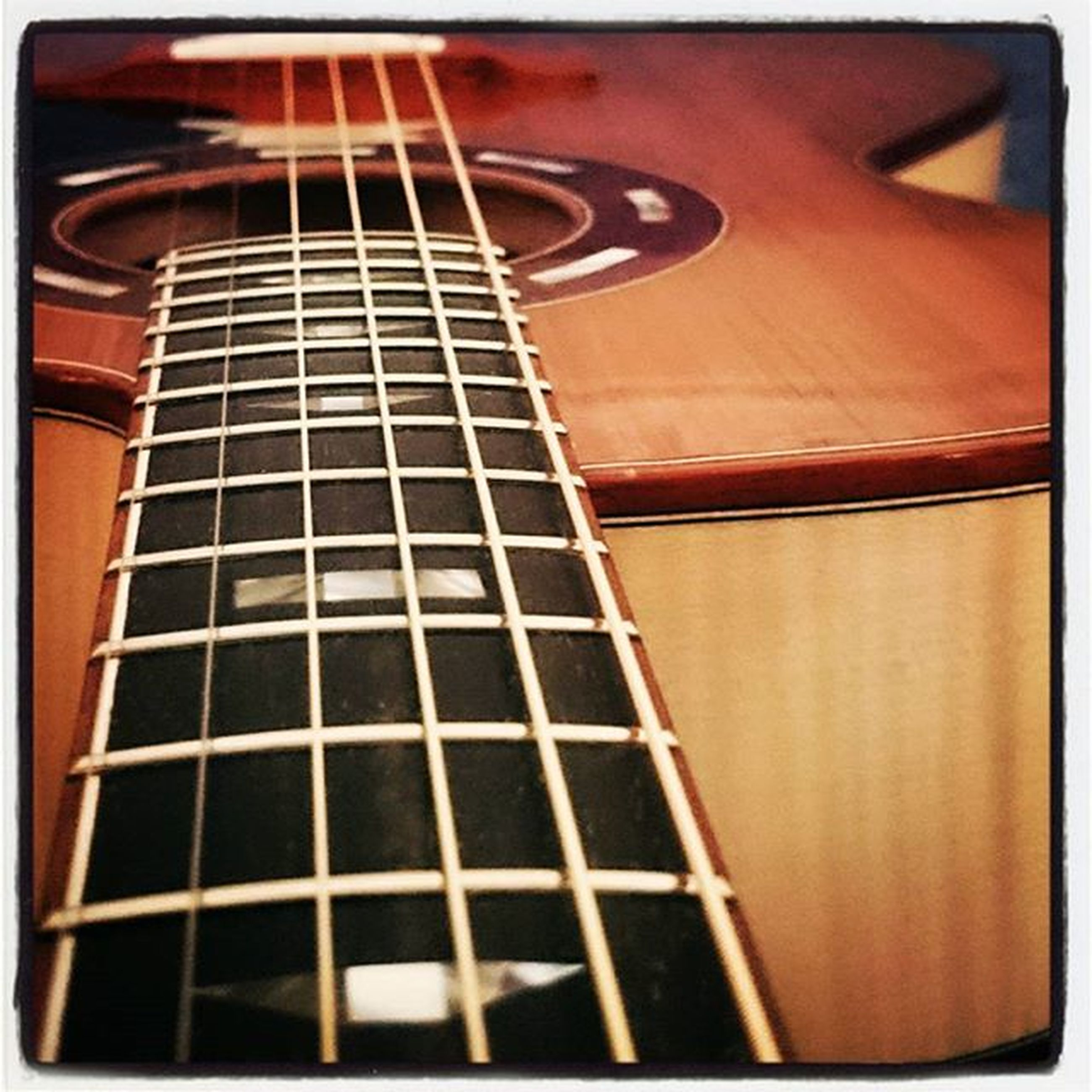 music, musical instrument, arts culture and entertainment, guitar, indoors, musical equipment, musical instrument string, auto post production filter, transfer print, modern, close-up, acoustic guitar, low angle view, string instrument, no people, pattern, selective focus, metal, tall - high, part of