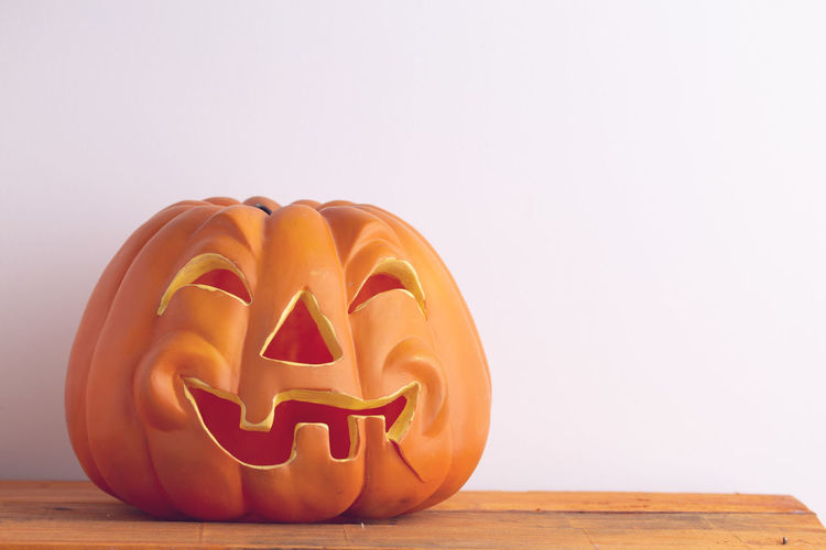 Close-up of pumpkin on table against white background