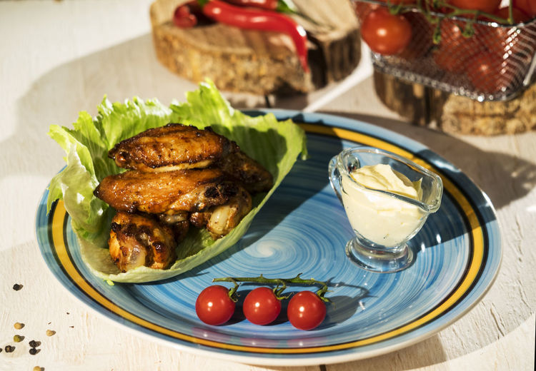 High angle view of chicken wings with cream and cherry tomatoes in plate on table