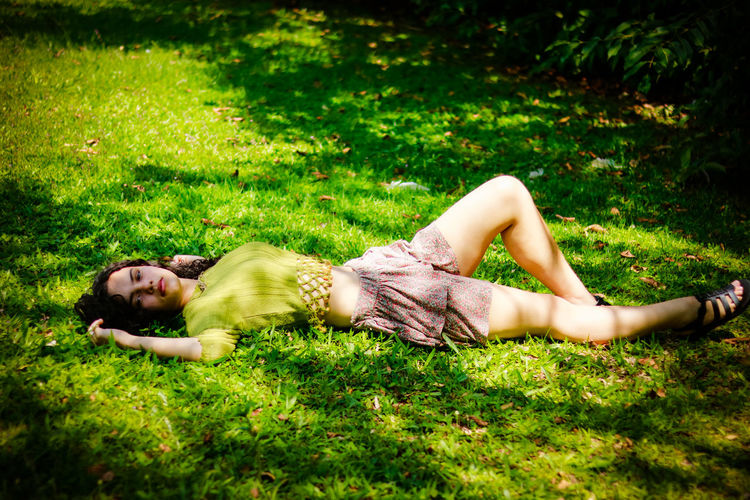 Teenage Girl Lying On Field At Park