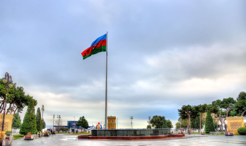 Scenic view of flag against sky in city