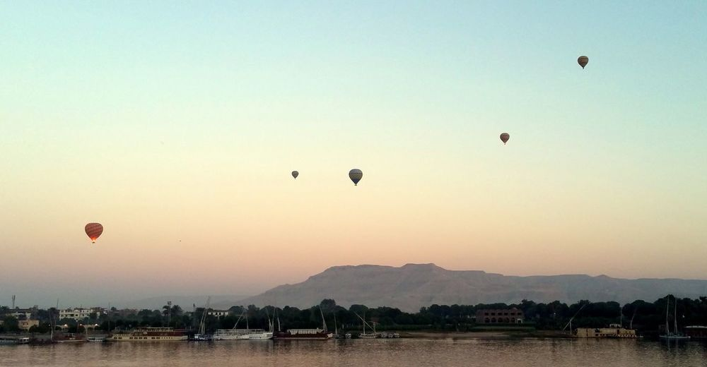Hot air balloons flying over river against sky at sunset