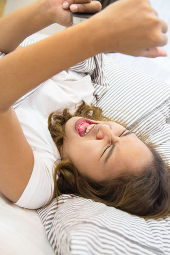 Woman Screaming While Holding Alarm Clock On Bed