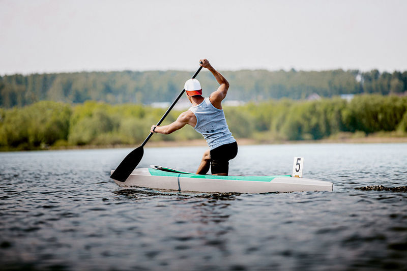 Rear view of man canoeing on lake