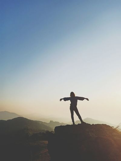 Silhouette woman with arms outstretched standing on mountain against clear sky