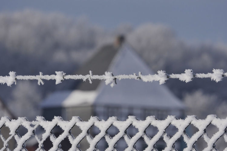 Close-Up Of Snow Covered Fence And Barb Wire Against House