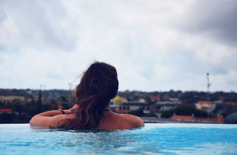 Rear view of woman swimming in infinity pool against sky