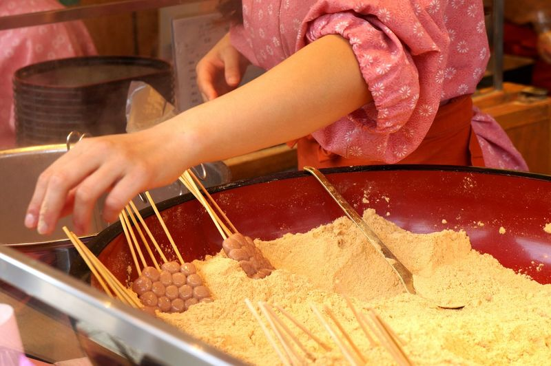 Midsection Of Person Making Candies At Shop