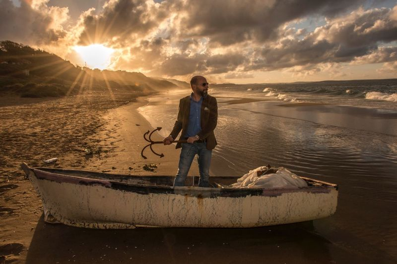 Man holding anchor while standing in abandoned boat at beach during sunset