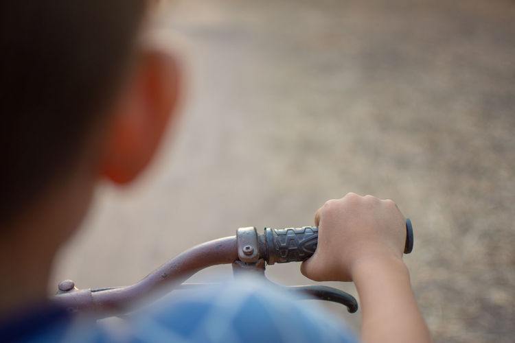Close-up of boy with bicycle on street