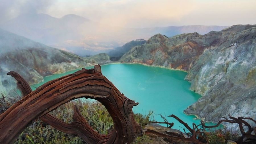 Scenic view of blue ijen crater against cloudy sky
