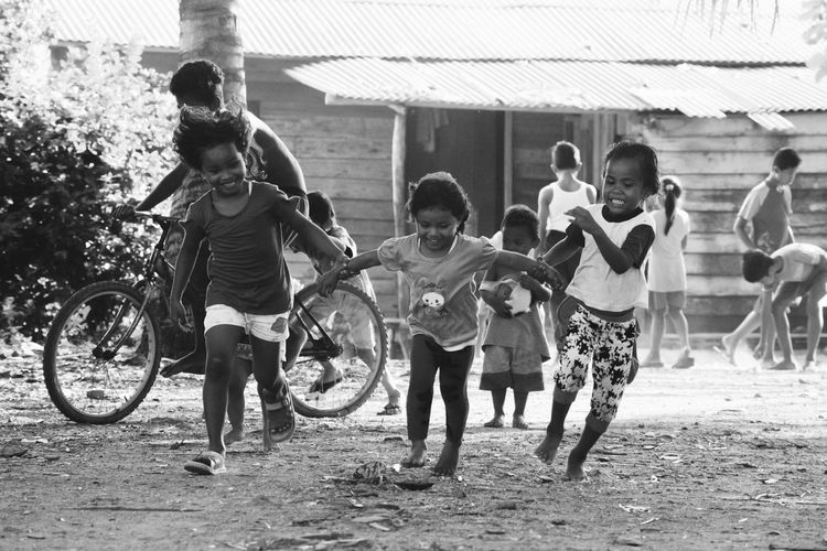 Cute siblings playing on dirt road at village