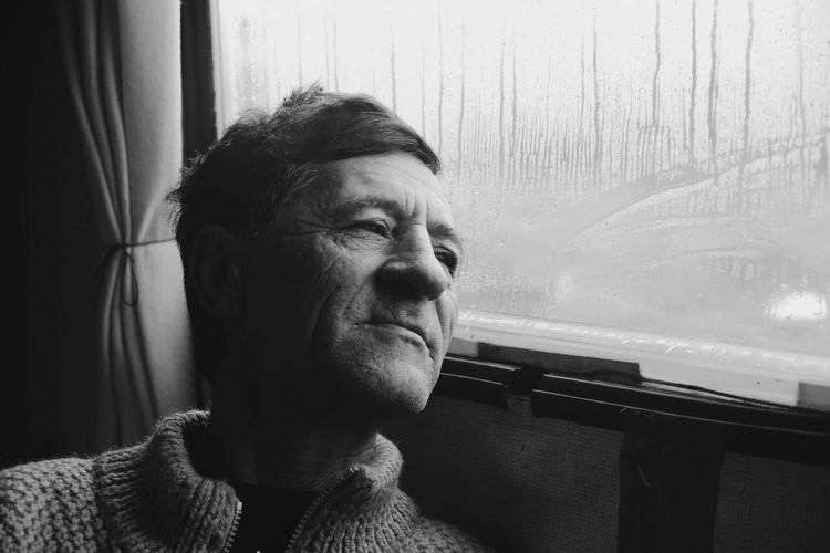Close-Up Of Man Sitting By Wet Train Window