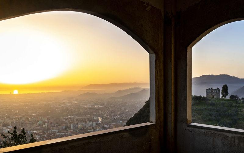 City seen through window during sunset