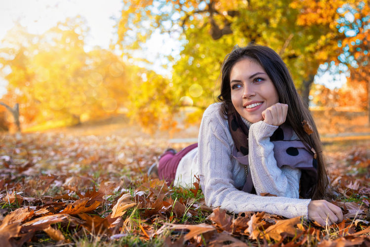 Attractive woman lies on the grass in the park during the golden autumn season Autumn One Person Smiling Plant Part Leaf Change Portrait Looking At Camera Leisure Activity Long Hair Happiness Lifestyles Tree Nature Warm Clothing Beautiful Woman Hairstyle Emotion Outdoors Young Adult Scarf October Autumn Fall Leaves Casual Clothing Park Golden Sun Sunshine