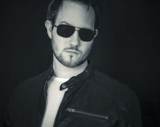 Portrait Of Confident Young Man In Sunglasses Standing Against Black Background