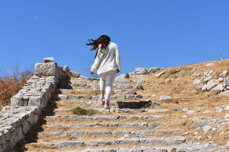 Woman standing on staircase against clear sky. ancient thera, santorini, greece