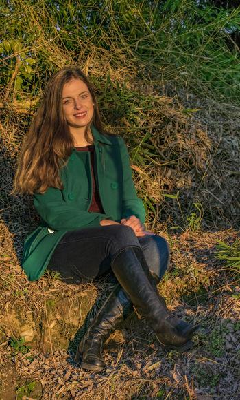 Portrait of beautiful woman sitting on field