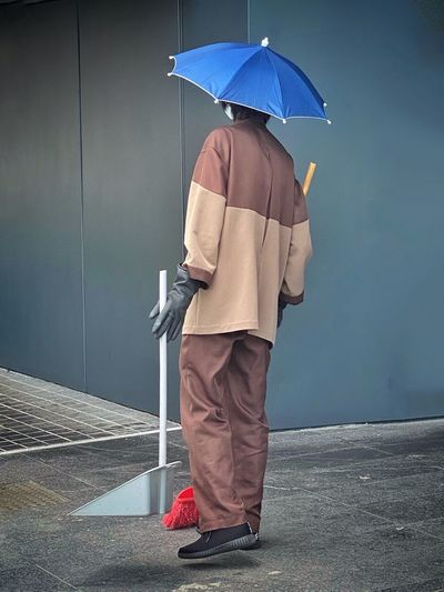 Rear view of man holding umbrella standing on rainy day