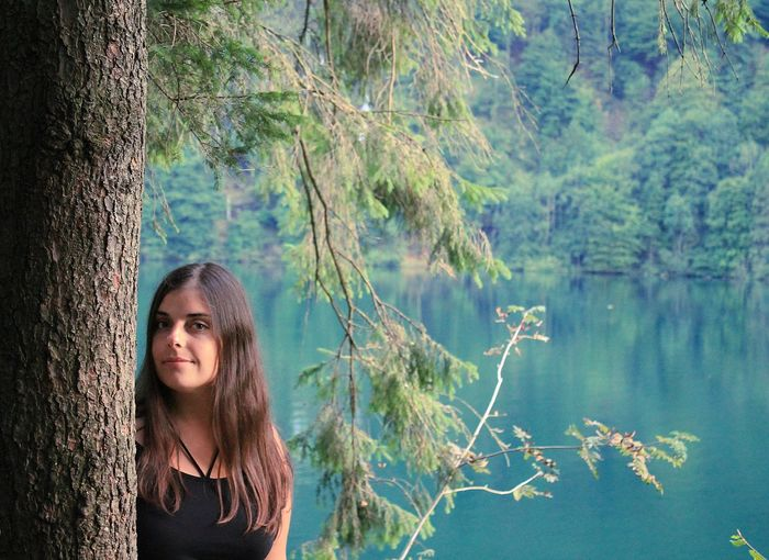 Portrait of young woman standing against lake