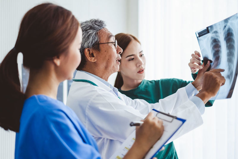 Doctor discussing with colleague over x-ray at hospital
