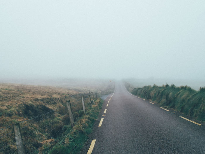 Road amidst landscape against sky during foggy weather
