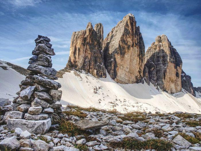 Stack of stones with mountain landscape along alps peaks, tre cime di lavaredo rocks in italy