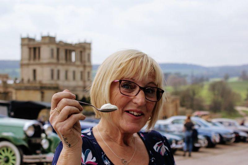 Portrait of woman holding yogurt on spoon
