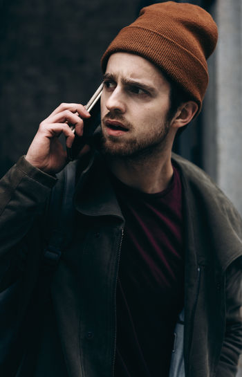 Portrait Of Young Man Looking Away While Using Phone