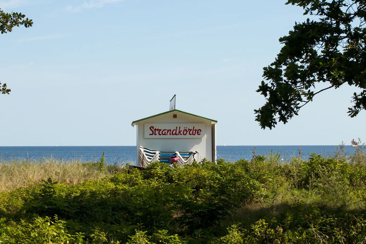 View of information sign on beach against sky