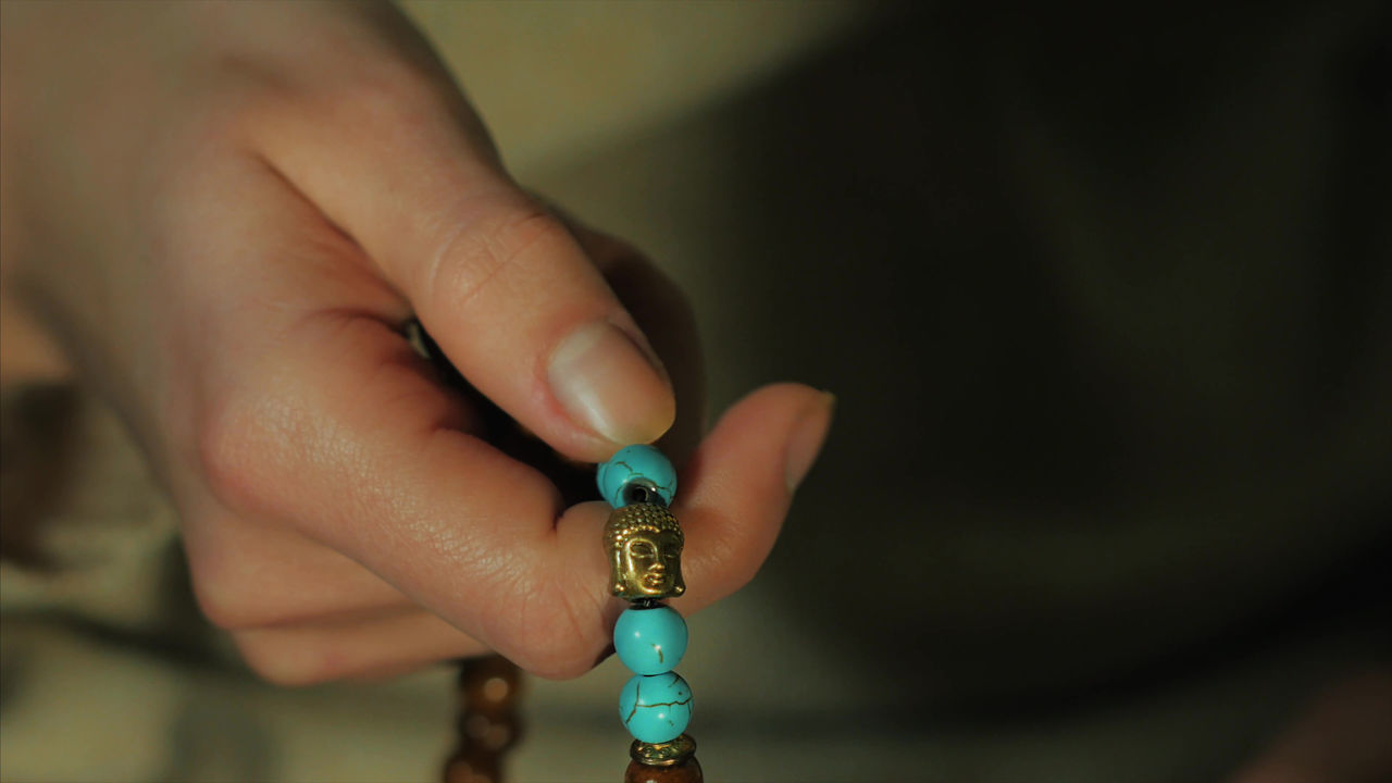 Cropped Hand Of Person Holding Bead Necklace
