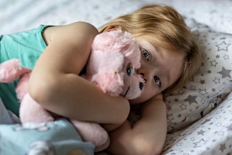 Portrait of cute baby girl with stuffed toy lying on bed at home