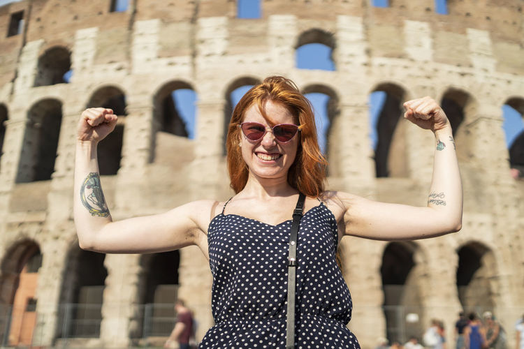 Young woman wearing sunglasses standing against built structure