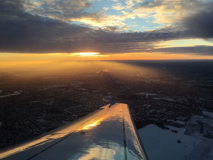 Cropped image of airplane wing over landscape during sunset