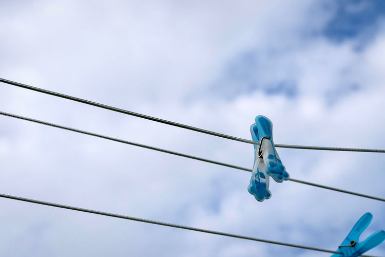 Low Angle View Of Clothespins Hanging From Clotheslines Against Sky
