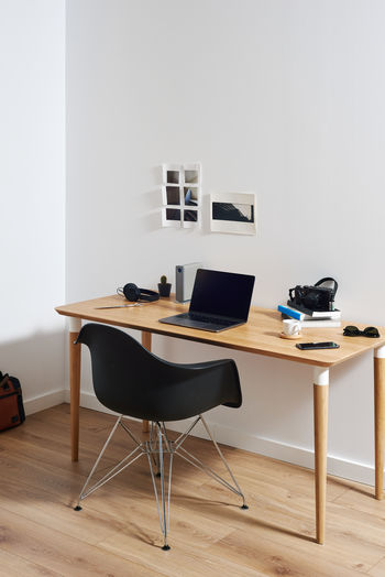 Table and chairs on floor against wall