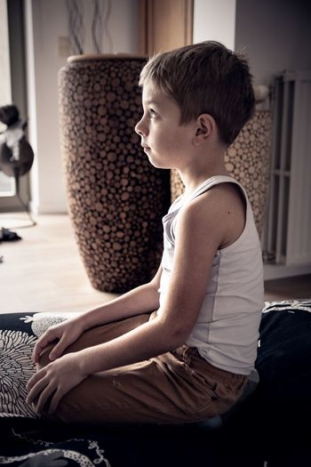 Side view of boy looking away at home