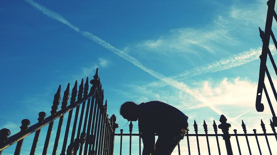 Low angle view of silhouette woman bending by railing against blue sky