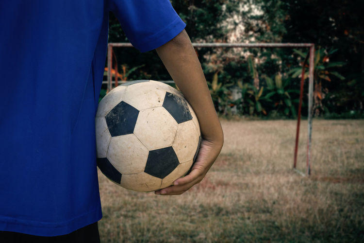 Midsection of man holding soccer ball