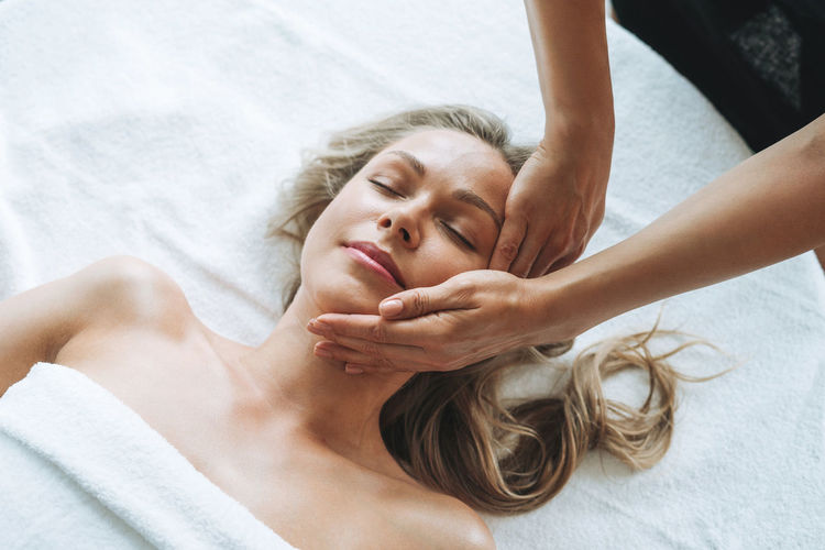 Attractive blonde young woman on couch with white linen enjoys hand facial massage in spa