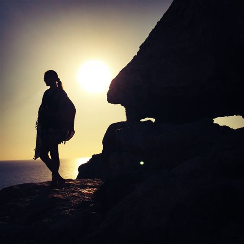 Side view of silhouette woman overlooking calm sea