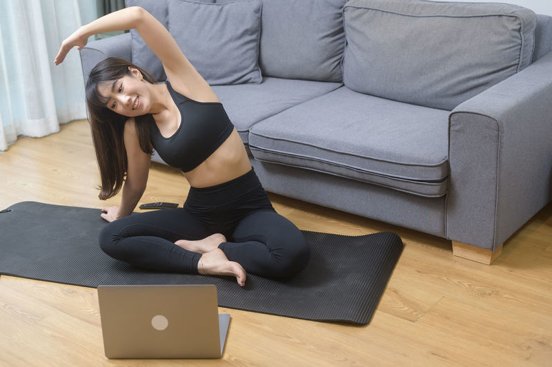 Full length of woman lying on floor at home